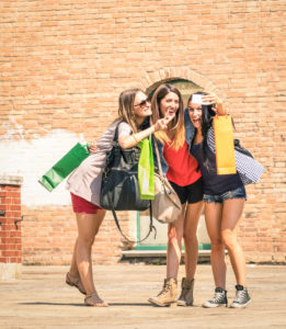 Group of happy best friends with shopping bags taking selfie